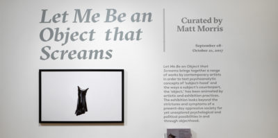 "An installation photograph of a title wall in large, grey, bolded text. The text is printed in vinyl and is attached to the wall and writes, ""Let Me Be an Object that Screams"". Below the title is an image of a black dress on white paper. The image has a thin, black frame. To the right of the image and title, a paragraph of smaller, bolded text, below a line that writes, ""Curated by Matt Morris""."