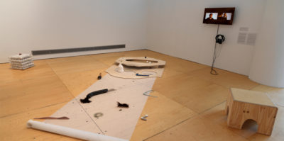 An installation photograph of the corner gallery space. Positioned on the floor, there is a translucent paper about two feet wide and eight feet vertically. Multiple found objects are placed on the translucent paper. A wooden circle protrudes from the ground at the top end of the translucent paper. A television monitor with headphones is mounted to the right wall. On the television monitor there is a middle aged person sitting.
