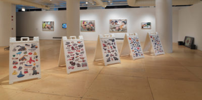 An installation photograph of the gallery space. Situated in the middle of the floor, there are four, white, plastic, A-Frame holders. Each holder is covered with sticker-like designs of assorted objects.