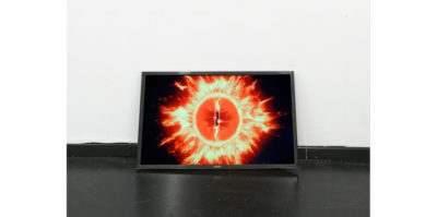 A photograph of a television monitor situated on the floor, against a wall. In the monitor is an image of a bright orange and yellow circular object. The circular object radiates from its edges a fire-like substance. The image is in front of a black background.