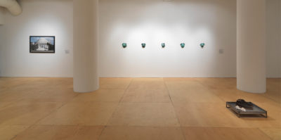 An installation photograph of a white wall in a gallery space. On the left side of the wall, a photograph of a federal building with white columns is mounted at eye-level. In the center of the wall, five green circular objects are situated in a horizontal line. Each object is nearly identical to the rest. There is about a foot of space between each green object.