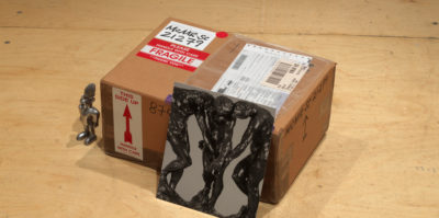 A photograph of a small cardboard shipping box. The box is wrapped with a shipping label.Placed against the box is an image of three sculptures of male figures. Sitting next to the box is a small, metal figurine.