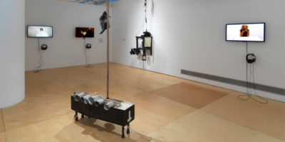 An installation photograph of a room in the gallery space. On the left wall, two television monitors are mounted on the wall. The monitor on the right is an image of a person with a white circular object, covering their body. The monitor on the right is of a person's foot in a dark room. Mounted on the right wall is an additional monitor and a square, three dimensional sculpture with four pegs. The monitor is paused on a film still of a middle-aged person sitting at a white table. In the center of the space, there is a rectangular, three dimensional object with six aluminum cans attached to the side.