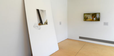 An installation photograph of two walls meeting in the corner of the gallery. On the left wall, a large, thick, white sheet leans against the wall. Centered in the middle of the sheet is a printed photograph of the same sheet. On the right wall, there is a framed, landscape style photograph. In the photograph there is a group of five people standing inside a room.