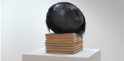 A photograph of a sculpture on a white podium. Eight, medium sized, light brown books are stacked vertically. Sitting on the stack of books is a black, circular object about the size of basketball.The circular object has black hair attached to its back side.