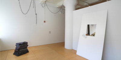 An installation photograph of the corner of a gallery space. On the right wall, a large, thick, white sheet leans against the wall. Centered in the middle of the sheet is a printed photograph of the sheet. In the left side of the space, on the floor, a vertical stack of black textiles are folded in squares and placed on top of one another. The size of the folded textiles from the floor is about two feet high.