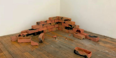 A photograph of a brick sculpture in the corner of the gallery. The brick layers form together to look like it was pulled from a structure's corner, as the shape extends in opposite directions, fewer bricks are stacked. The bricks are orange in color, with stains of black and grey.