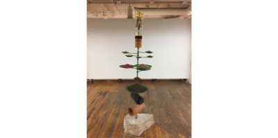 A tall standing sculpture in the middle of the room consists of a steel rod protruding from a large limestone base. Thread through the bottom of the rod directly above the limestone is a fragment of drainage tile. Above this, an assortment of green metal plates extends upwards containing various collections of natural debri, such as soil, dirt, corn and bird seed. At the very top of the sculpture is a collection of vestibules containing assortments of different fertilizers, bird feed, and processed materials.