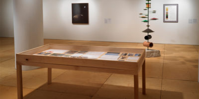 A installation photograph of a wooden and glass vitrine with documents and photographs inside. Behind the virtine, is a tall standing sculpture in the middle of the room consisting of a steel rod protruding from a large limestone base. Thread through the bottom of the rod directly above the limestone is a fragment of drainage tile. Above this, an assortment of green metal plates extends upwards. Against the wall that is behind a sculpture, are two different two-dimensional framed prints, about six feet apart from one another.