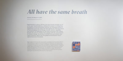 """An installation photograph of the introductory paragraph text for the exhibition printed on the wall. The entire text is about 3 feet long, printed in a light grey font. The title is larger than the rest of the text which reads, """"All have the same breath""""."""