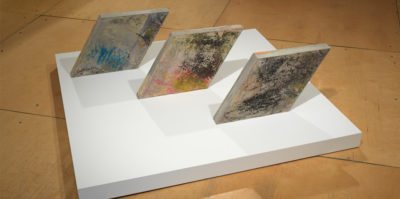 Three rhombus shaped concrete slabs parallel to each other resting on a white square platform. Upon the surface of the slabs there are oil pastel rubbings in various colors, the texture resembling crayons. (sky blue, hot pink, orange, and avocado green)