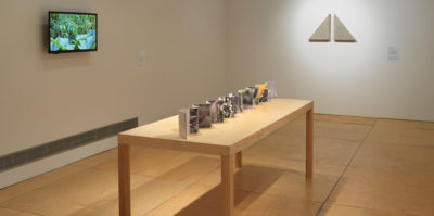 An installation photograph of three objects in the gallery. Displayed along a table is an accordion book with one whole side being a panorama of a garden, while the opposing side an outline of the geographic lands of planet Earth..On the wall adjacent to the accordion, is a video that is a documentation of moving plants accompanied by the sounds of wildlife. On the back centered wall there are two back to back, white, right angle triangle sculptures are positioned on the wall.