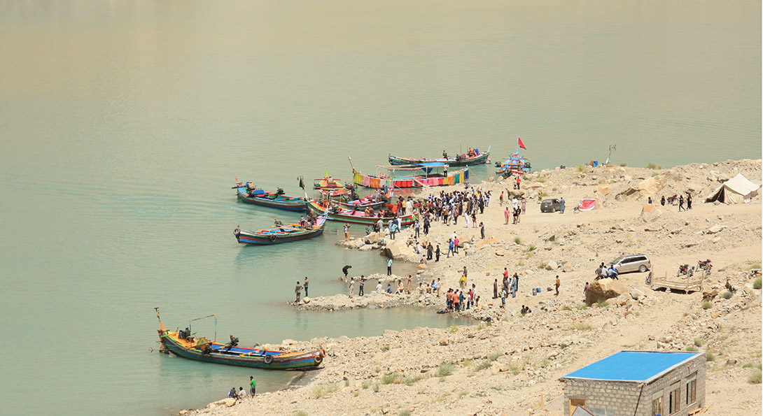 A photograph taken from above of people gathering on a beach. Six smaller boats, painted with bright colors, are lined up on the shore line.