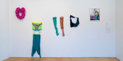 An installation photograph of five different materials mounted to the white gallery wall. The first material on the far left is of a bright pink cloth, weaved together in a circle. The second material to the right is a two-piece outfit with a blue mermaid tail. The top half of the two piece is a green and black and white checkered material. The third material are two full-sleeve gloves. One glove is teal and the other glove is a burnt, sparkling orange. The fourth material is in the shape of a blue purse, connected by two silver rings. The fifth and final piece to the right is a framed photograph of a person wearing the following materials that are mounted on the wall.