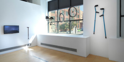 An installation photograph of two gallery walls. The gallery wall on the right has three windows. Hanging by an invisible wire in front of the window are two wheels and a chair piece. Next to the window is a mounted pair of blue crutches. On the wall left to the window is a mounted television monitor of a dark blue image. To the right is a mounted walking cane.
