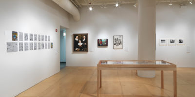 An installation photograph of a large coroner of the gallery space. On the right wall, six images are mounted on the wall. A large circular sits in the center, with three of the images on its left, and three on its right. On the other left wall, a series of unframed papers attached to the wall in two rows. On the floor in front of the two walls, a large, six foot long wooden vitrine is placed, showing multiple documents.