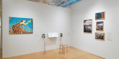 An installation photograph of the corner gallery space. The corner meets in the center of the photograph. The wall to the left has a large painting of a person painted in orange tones, with a blue background. Two pairs of headphones and a podium with documents is situated to the right side of the painting. On the right wall, there are four, wooden framed industrial photographs, mounted in a collage design.