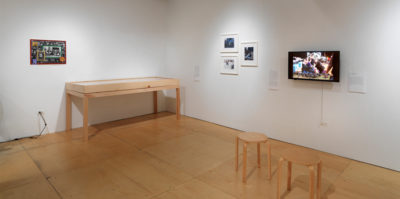 An installation photograph of the gallery. On the left wall, a small 12x16 image is framed and mounted. Against the left wall is a six foot long wooden vitine showcasing multiple documents. On the right wall, a tryptic of three 10x12 images with white frames are mounted. To the right of the tryptic is a television screen. The video still has three middle-aged people in conversation.