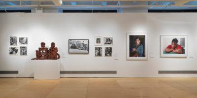 An installation photograph of seven artworks on a gallery wall. Starting from the far left side object, there are four small, black and white photographs in a white frame. The four photographs are aligned in a square formation. The second object is a brown clay sculpture of a person sitting down. The third object is an 11x17 black and white photograph of multiple people in a field. The fourth object is a series of four photographs aligned in a square formation. The top left photograph is in color, and the three additional photographs are in black and white. The fifth object is a large, framed, digital, portrait photograph of a younger-aged person. The sixth object is an additional large, framed, digital, portrait photograph of a younger-aged person by the same artist.
