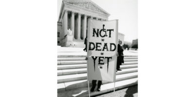 "A black and white photograph of a person standing outside on the steps of a federal building. The person is holding a sign that is as large as their body. The sign writes, ""NOT DEAD YET"". In the ""O"" letter of ""NOT"", the ""O"" is designed to look like the accessible wheelchair symbol."
