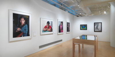 An installation photograph of the gallery space. In the center of the photograph, the wall on the left and right sides meet in the corner. On the left wall, four, large, white framed portraits are mounted. Each portrait is a portrait style photograph of a younger-aged person looking at the camera. On the right wall, two images are mounted on the wall in black frames. The image on the left has a blue shape in the middle with a black background and light green sides. The image on the right is a black and white drawing of a person standing. Centered on the gallery wooden floor is a large wooden and glass vitrine with documents inside.