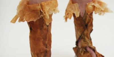 A photograph of a footwear art piece on a pair of legs. The footwear is made out of a brown leather material, and thread together with black thread. On the top of the leather footwear, the leather is folded over in a lighter brown color.