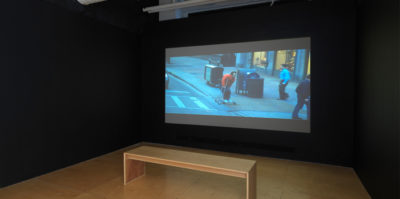 An installation photograph of the film room in the gallery space. The walls are black with a wooden bench in the center. Projected to the wall is a film still of a middle-aged person on a skateboard. They are skating on the sidewalk, wearing a red sweater, and two people are walking by them.