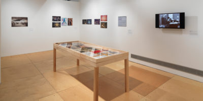 An installation photograph of the main gallery space. A large, seven foot long, wooden and glass vitrine is centered in the middle of the photograph. Inside the vitrine is a variation of photographs and documents. On the walls surrounding the vitrine are multiple, unframed images. On the wall to the right of the virtine is a modern-day television monitor with a black and white film still.