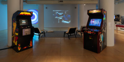 An installation photograph of the center of the gallery space. The left and right sides each have two ceiling length, white pillars, all together creating a square structure. Situated against the front two, left and right pillars there is each one video game console. Behind them is a grey rug with three white lounge chairs. On the back wall, a still from a projected video is displayed. The video still is of two middle aged people sitting next to eachother.