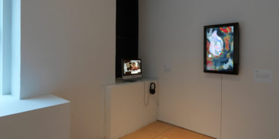 An installation photograph of the corner of the gallery space. On the left side of the corner, A small Mac monitor screen is playing a video. On the right wall of the corner, there is a television monitor positioned vertically on its side, with an abstracted blue, red, and white fluid design of different circular shapes.