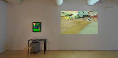 An installation photograph of the gallery wall. On the left side, a television monitor is mounted and is about the size of a 17x20 inch painting. The moniter has a saturated image of a tree in a park on its screen. Below the monitor, a metal black desk is situated against the wall with two books and a document. Underneath the desk is a two-door, metal filing cabinet. Parallel to this installation is a large, 4x6 foot projected image. The image is of a mountain landscape above a sand dessert with hills.