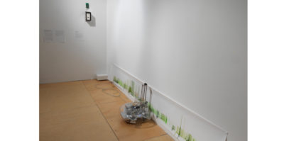 An installation photograph of two of the white gallery walls. On the bottom right wall, a long, two foot high print is displayed, touching the ground. In the center of the print, sitting against the wall, is a glass object with computer system objects inside. On the left wall, three white labels are placed in the center.