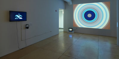 An installation photograph of the exhibition. The space lighting is darker. On the left wall, there is a flat-screen television with a film still of a black background and a blue design. A pair of headphones is attached to this screen for listening. On the wall in the center of the photograph, a large image of multiple circles is projected onto the white gallery wall. The projection size covers the entire gallery wall.