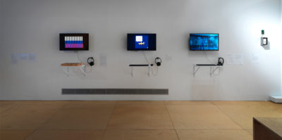 An installation photograph of the exhibition. This photograph is of one of the gallery walls. Mounted on the wall is three television monitors with headphones attached. Mounted on the wall below the televisions are individual shelves with square objects placed on top.