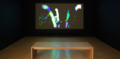 An installation photograph of the film screening room in the exhibition. The film is projected against the wall. The scene in the film still is of a middle-aged person that is pointing to an abstracted design. The film still is highly contrasted, with dark shadows. The abstracted light design is of three large, bright lines. To the left of the lines is a blue, green and red rainbow-like gradient.