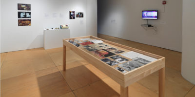 An installation photograph of the main gallery space. A large, seven foot long, wooden and glass vitrine is centered in the middle of the photograph. Inside the vitrine is a variation of photographs and documents. On the wall to the right of the virtine is a television monitor. On the monitor's screen is a blurred circular image in pink and blue tones. The wall on the left of the vitrine has five, unframed photographs positioned on the wall.