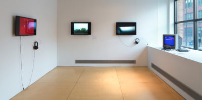 An installation photograph of the side gallery space. The right wall has a large window letting in natural sunlight. On the platform below the window, a small, 90's style television is situated in the corner with a blue screen. The center wall has two, modern day television monitors of green and blue landscapes on the screens with headphones attached. The left wall also has a modern day television monitor mounted in the center. A pair of headphones is attached to the monitor. The screen has a red maroon color.