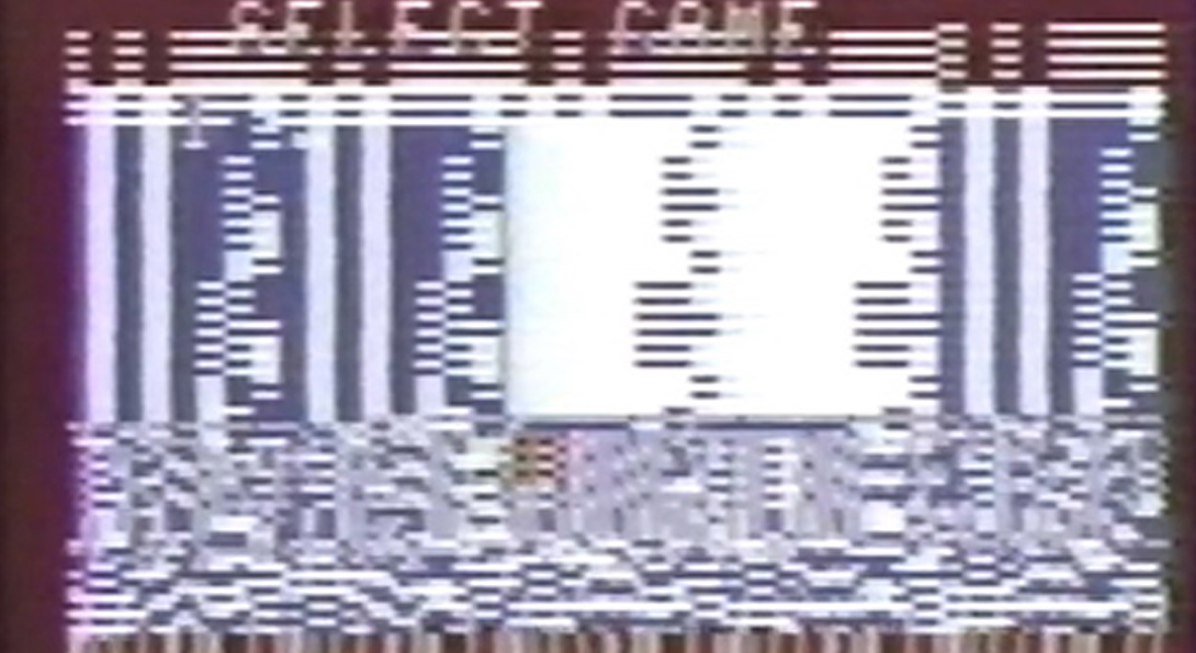 "An image of a pixelated screen with static. On the center top of the image there are letters with the words ""Select Game"". The letters are fading into the gray pixilation."