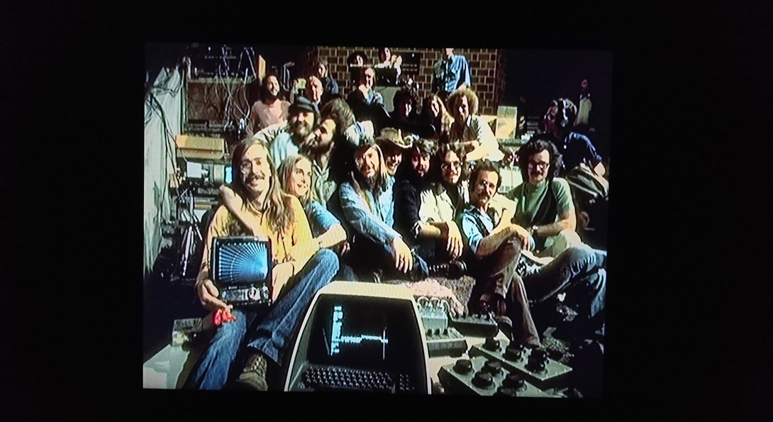 A photograph of fifteen people in a group, sitting closely. They looking at the camera, smiling, and holding 1970s computer softwear.