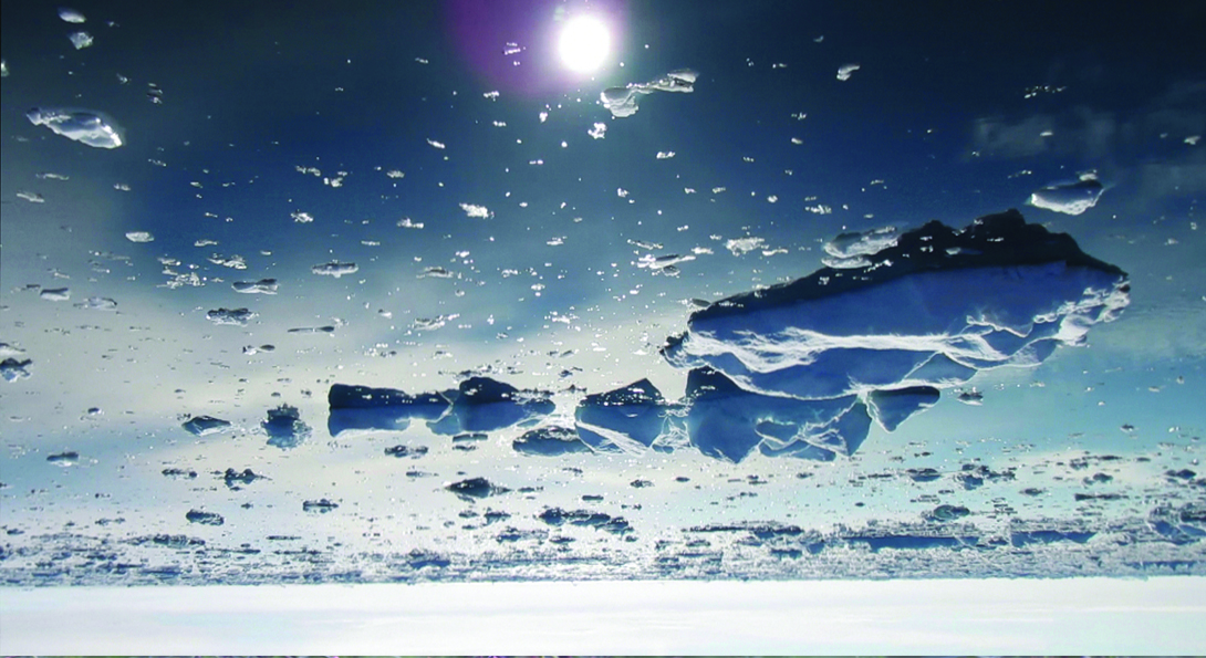 An upside-down photograph of melting glaciers in water. A white, circular glare from the sun is in the top center.