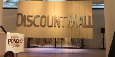 """An installation photograph of a large sculpture that hangs from the ceiling, about 3 feet above the floor. The sculpture is a white rectangle, resembling an outside of a building. Letters, about half the size of the square, read, """"Discount Mall"""". The letters are made of the same material, but painted silver, resembling a building sign."""