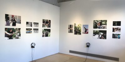 An installation photograph of one of the gallery spaces. Taken from the corner of the room, two walls meet in the center of the photograph. On the left whtie wall, eight square unframed photographs of people participating in activities outside. Below the photographs is a plug in with one pair of listening headphones. The right wall also has eight unframed photographs, organized of people participating in activities outside. Underneath these photographs, another set of headphones is positioned on the wall.