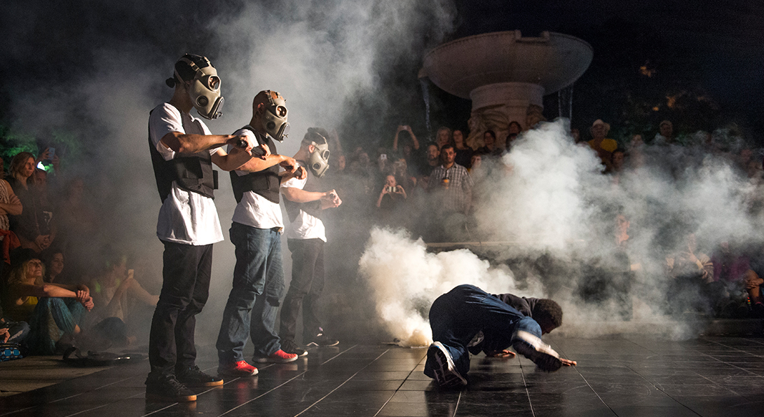 A photograph of a performance, taken at night-time. A group of spectators are circled around them as they perform outside, under a light. Three performers are standing in a line with gas masks on and bullet-proof vests. There is a smoke effect behind them. They are wearing jean pants and white T-shirts. There is a person on the ground in front of them.