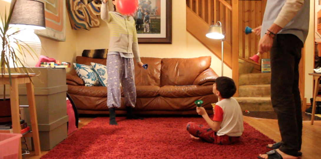A photograph of a video still from Sensitive Equipment. The video still is in a living room setting. A young person is sitting on a red carpet on the floor. They are looking upwards at another young person, standing, holding a pink balloon. They are both wearing pajamas and engaging in front of a brown leather couch. Behind the couch, there are wooden stairs leading up to the top center of the photograph. On the right side of the photograph, the lower body of an older person is standing with toys in their hand.