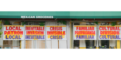 """A long, landscape photograph of a mexican grocery store. Five window signs have bolded text in red, orange, blue and yellow, printed on white poster paper. The sign in the center window reads, """"CRISIS. INVISIBLE. CRISIS"""". Above the windows is a green rooftop that reads, """"Mexican Groceries""""."""