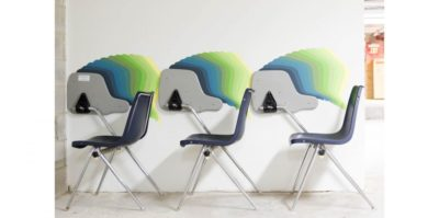A photograph of three plastic and metal, blue school chairs are positioned against a white wall. The top of the desk, connected to each chair, is flipped upward against the wall. A design takes the shape of each of the chair's desks and is painted in a gradient from blue, green, and then yellow.