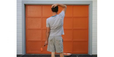 Photograph of a middle-aged person standing in front of an orange garage door. The person, wearing gray clothing, is holding an orange roller paint brush. Beside them, a tin of orange paint sits on the floor.
