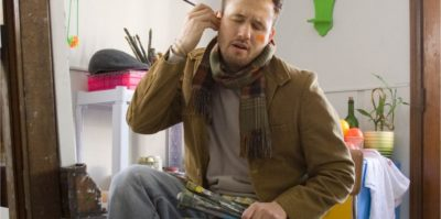 A photograph of a middle-aged person is sitting in a chair holding paint brushes. They are wearing a brown jacket, jeans, and a brown scarf. Behind them, there is furniture holding plans, paint brushes, and a white towel.. The person is holding a paintbrush, sticking it in their left ear, with orange paint on their right cheek. Closing their eyes, their face holds a displeased reaction.