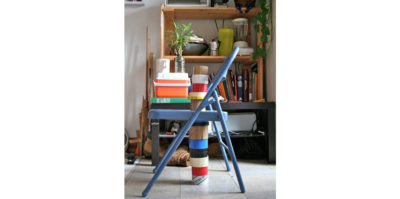 A digital, portrait-style photograph of a light blue, small, metal chair. The photograph is taken closely, so the chair fills up most of the frame. Books, an orange cooler, and a white coffee cup are stacked on top of the base of the chair. 13 rolls of electric tape, in multiple colors, are stacked below the chair, and continue to stack upwards from the base of the chair. Behind the chair, a wooden bookshelf holds multiple books, cups, and green plants.