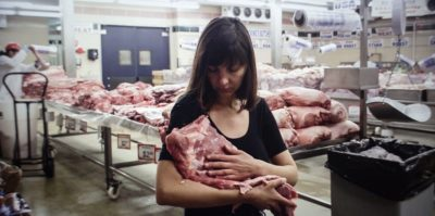 A photograph of a middle aged person holding a large, square piece of raw meat. They are holding it in their left arm, and their right arm is placed on the front side. The person is standing inside a meat producing facility. Behind them is a large table of stacked, multiple square pieces of raw meat. Another person, in a white sanitary suit is working on the table behind them.